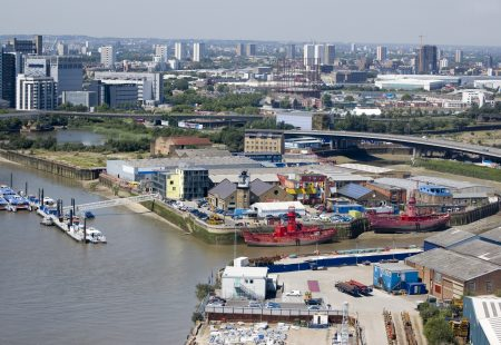 """View from above of the River Thames and River Lea and the island with Trinity Buoy Wharf in Newham, East London. East India Dock basin behindView from public transport."""