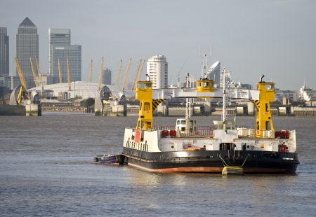 A view of the Woolwich Ferry with the towers of Canary wharf and the millenium dome in the background.